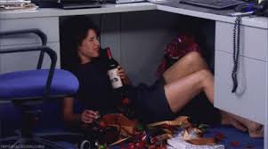 lady under desk with a bottle of wine