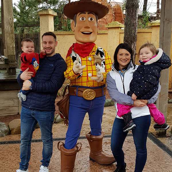 Family posing with Woody from Toy Story