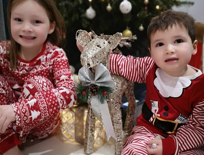 Two children dressed in Christmas clothes sat by Christmas tree