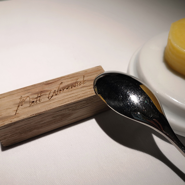 spoon resting on a wooden block in restaurant