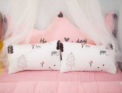 two pillows on a pink bed