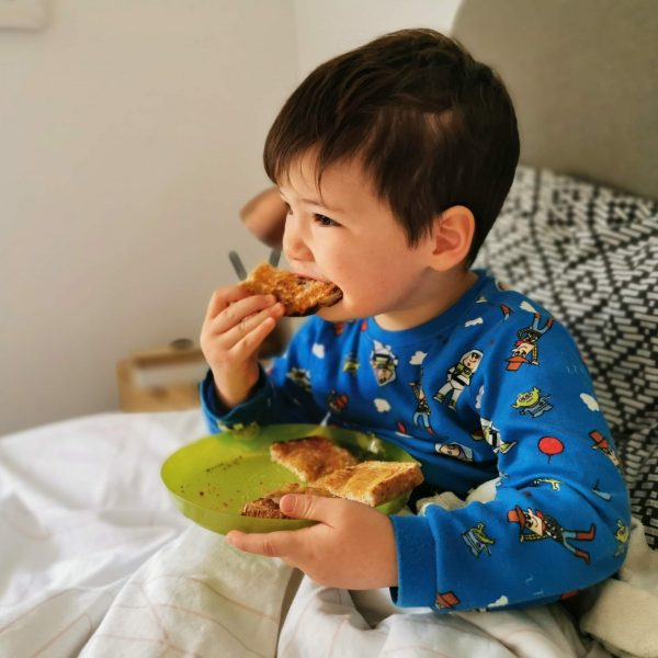 young boy eating toast in bed