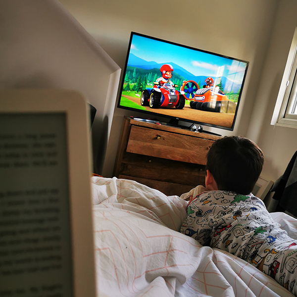 young boy in bed watching TV