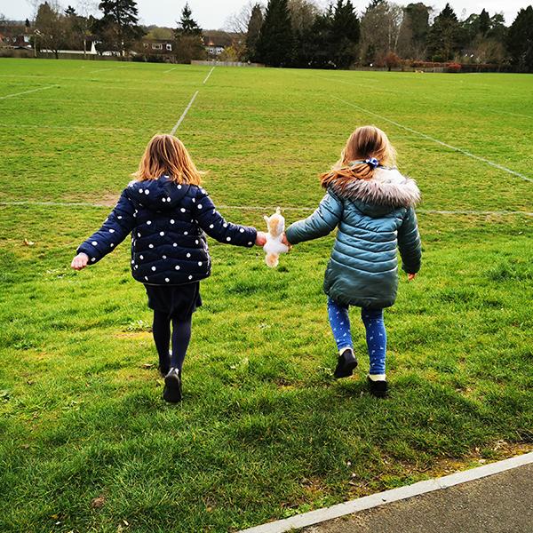 two girls running across field