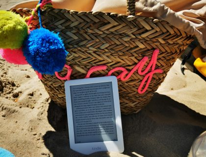 reading - kindle lent against beach bag on the sand