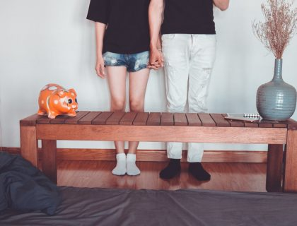 man and woman holding hands by coffee table