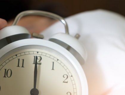 person holding an alarm clock in bed