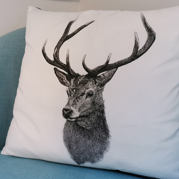 white cushion with a black deer pictureon it