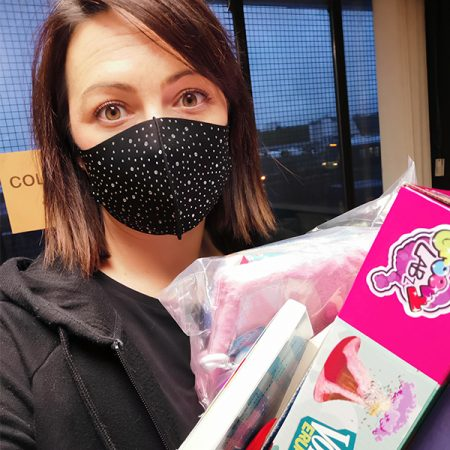 lady in face mask with toy boxes in hand