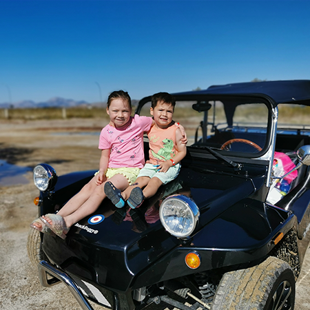 young boy and girl sat on bonnet of beach buggy