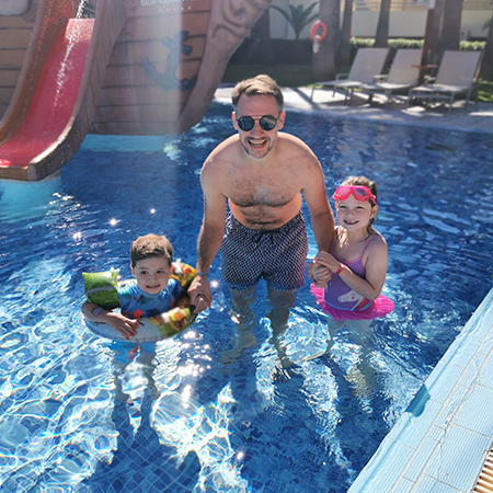 dad and two children in swimming pool