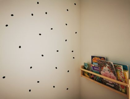 bookshelf next to spotty wall in playroom