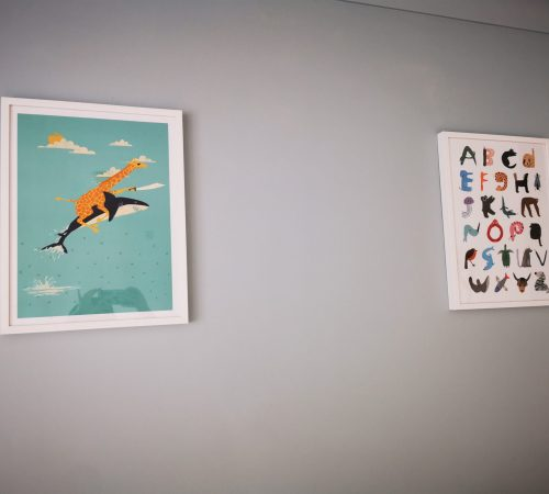 two colourful pictures on playroom wall
