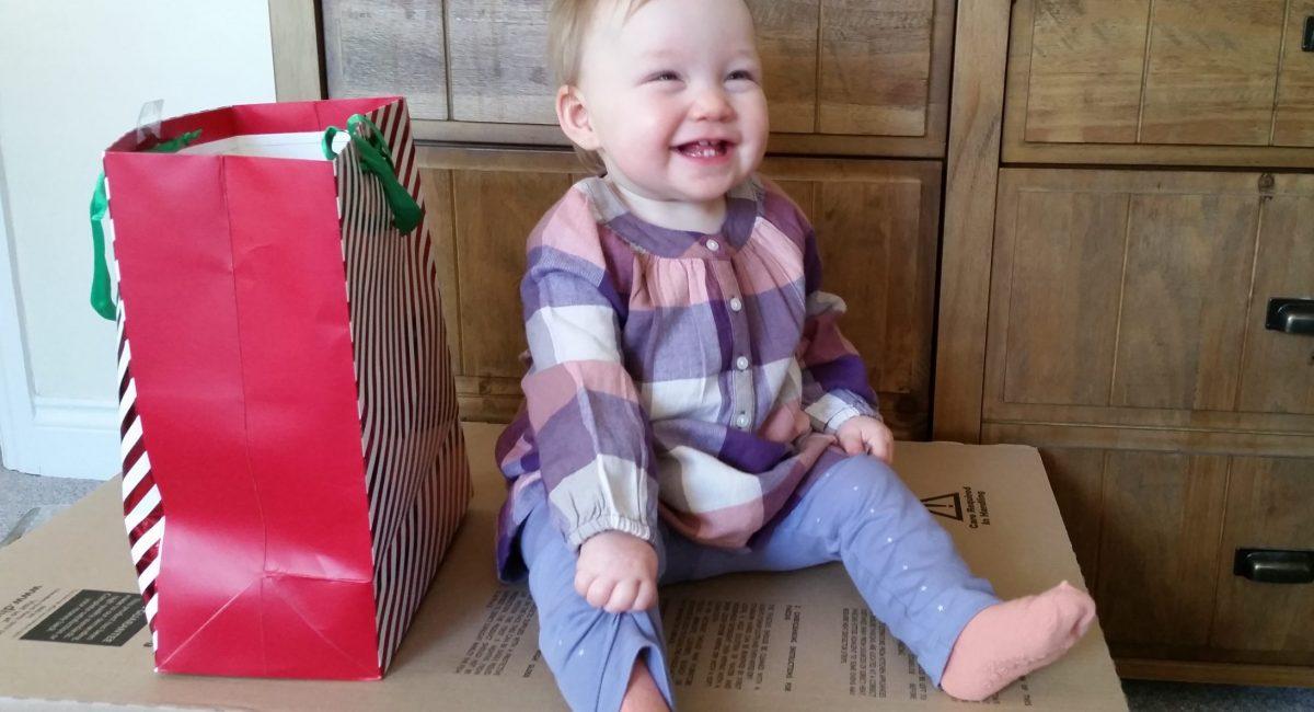 baby girl sat on cardboard box