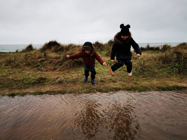 children jumping into a puddle in mid air