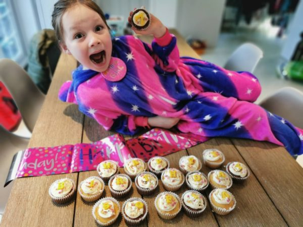 seven year old girl holding up birthday cupcakes